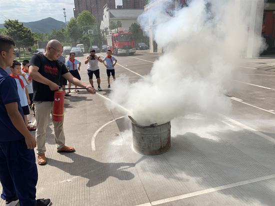 消防队员们耐心的向学生们讲解如何使用灭火器灭火的知识。 王玮琦 摄