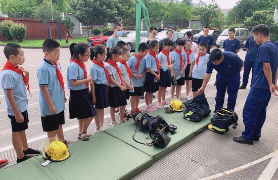 消防队员介绍各类车辆与器材装备的使用方法、功能、用途等。 王玮琦 摄
