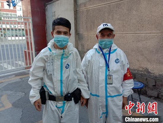 抗疫一線,穿著防護服的阿布都外力·買買提艾力與父親。 楊佳瑋 攝
