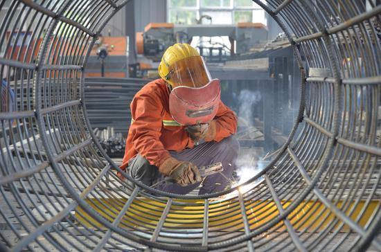 员工顶着高温焊接桥墩钢筋笼。龙杰 摄