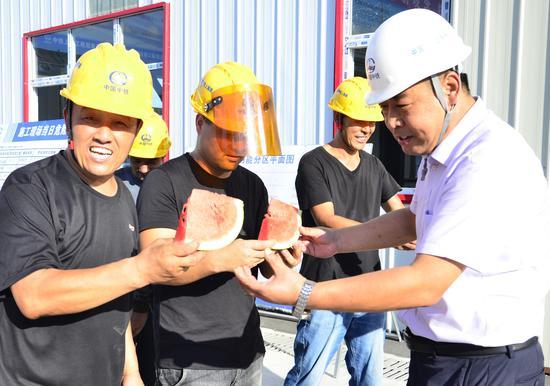 中铁上海工程局杭温铁路项目三分部党支部书记兼工会主度王俊清把西瓜送到一线员工手上。龙杰 摄
