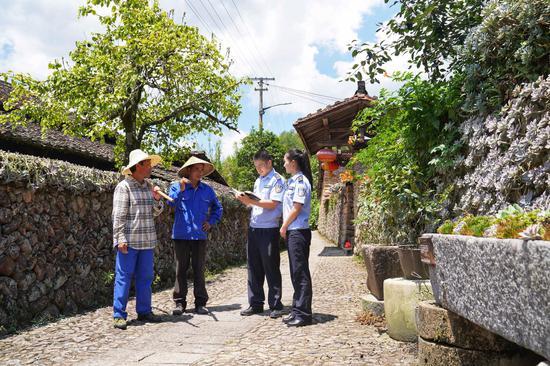 """景宁民警走访深垟村农户,为农户生产生活编织""""安全网""""。  梅婷 摄"""