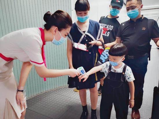 王妮娜给旅客测量体温(左)。长龙航空供图