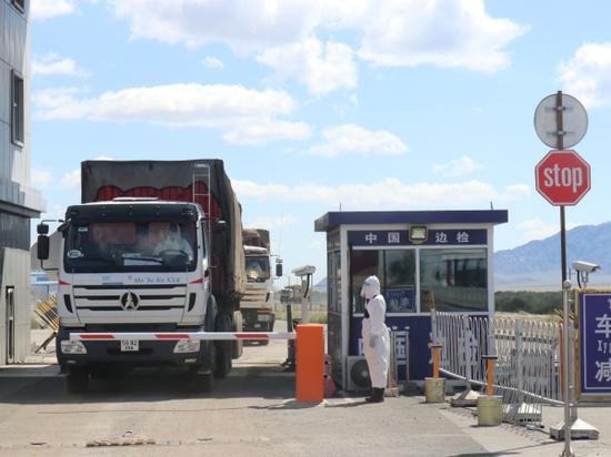 图为在新疆塔克什肯∞口岸入境车辆在国门☆等待进入限定区域。