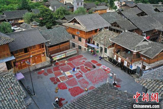 增沖侗寨村民在戲臺前院壩晾曬辣椒(無人機照片)。吳德軍 攝