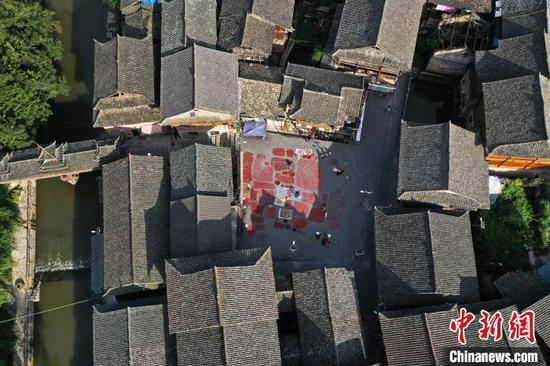 增沖侗寨村民在戲臺前院壩晾曬辣椒。吳德軍 攝