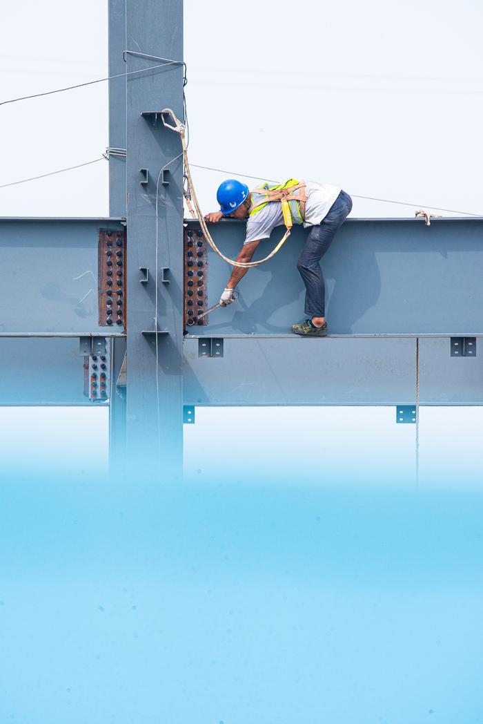 钢结构工人在拧紧衔接螺丝。宁波南商管委会供图