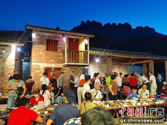 圖為游客們參加瑤族特色長桌宴。茂南·金秀扶貧協作辦   供圖