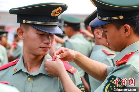 图为一名战友为退伍老兵卸警衔。武警贵州总队机动支队供图
