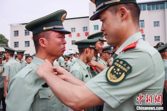 图为一名战友为退伍老兵卸警衔。 武警贵州总队机动支队供图