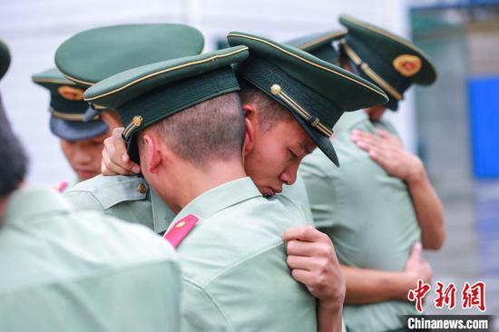图为退伍老兵和战友相拥告别。武警贵州总队机动支队供图