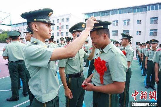 图为一名战友为退伍老兵卸帽徽。武警贵州总队机动支队供图