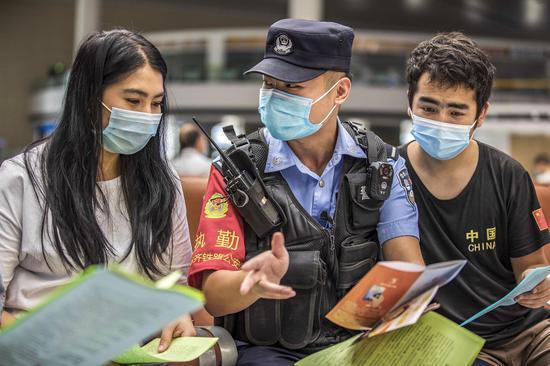 民警向准备乘坐T136次前往广州上学的大学生宣讲防电→→信诈骗知识。