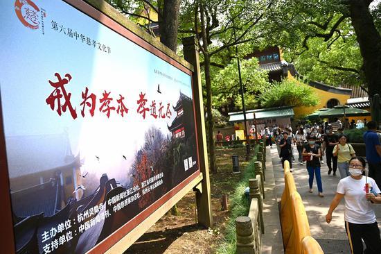 """灵隐寺内的""""2020年第六届中华慈孝文化节""""宣传栏吸引香客眼光。  张茵 摄"""
