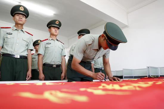 退役老兵在队旗上签名。
