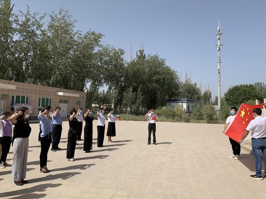 """且末镇各族干群正在烈々士纪念牌前,进行""""我是中国公民""""集体宣誓。"""