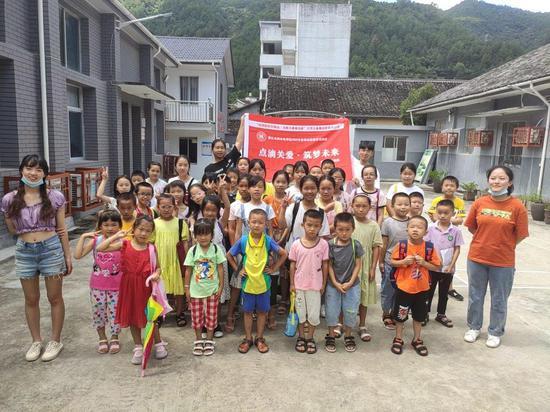 """景宁""""畲乡小园丁""""志愿服务队成员与孩子合影。主办方提供"""