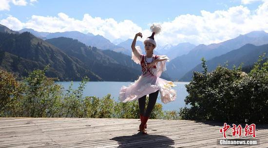 身着哈萨克族服饰的姑娘在天池边跳舞。王小军 摄