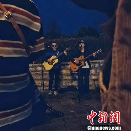 图为陈昌海、杨志街边演唱。受访者供图