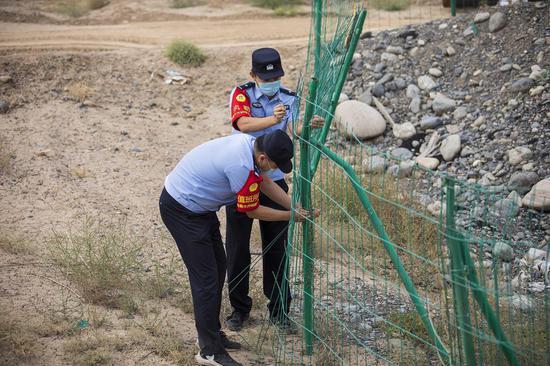 民警对铁路附近施工现场临时护栏进行加固。