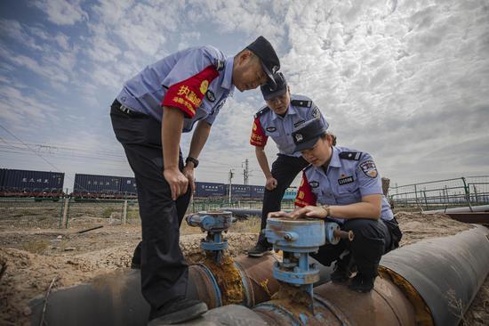 民警对穿越铁路天然气管道压力表进行安全检查。