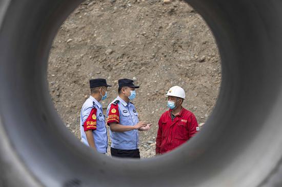 民警对穿越铁路石油管道施工方负责人进行安全宣传。