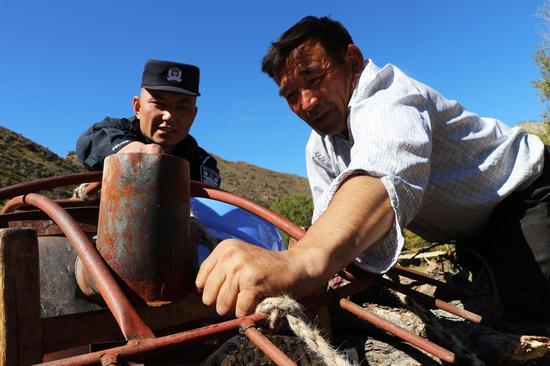 民警帮助牧民收拾下山的物品。