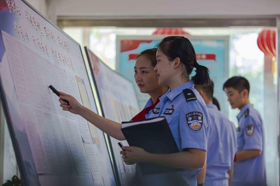 青年民警对中国人民警察训词硬笔书法比赛展板前交流书写体会。
