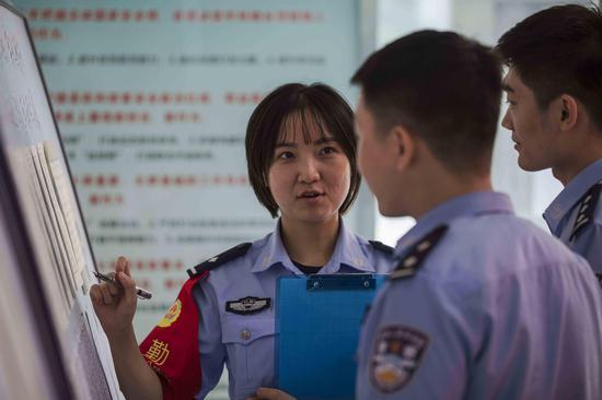 青年民警对中国人民警察训词的硬笔作品进行学习交流。