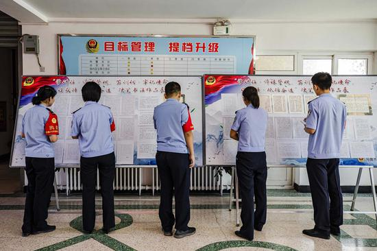 青年民警认真观摩书写中国人民警察训词硬笔书法展板。