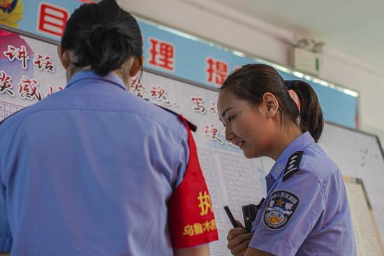 青年民警在展板前认真学习优秀硬笔书法作品。