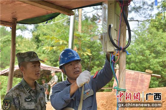 为部队封控点抢修送电并讲解故障处理方法。易欢 摄