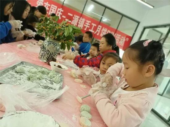 二源镇文化礼堂内,孩子们正在制作月饼。文成供图