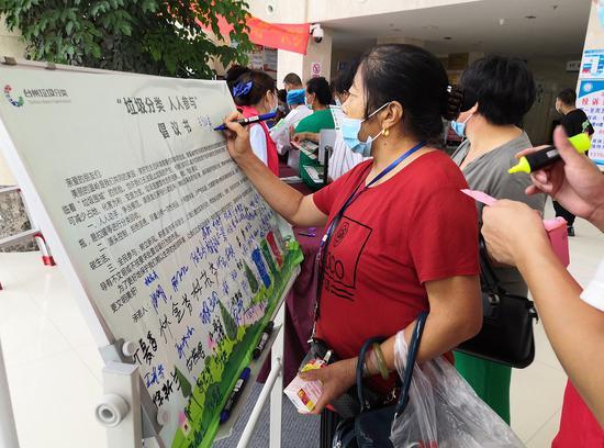 市民在垃圾分类倡议书上签字 陈爱君 摄