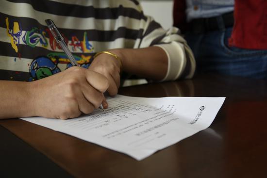 """李小华在""""中国人体器官捐献""""志愿书上写下名字。 徐冬梅 摄"""