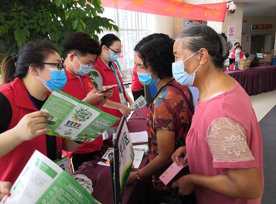 志愿者向市民宣传垃圾分类知识 陈爱君 摄