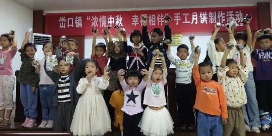 峃口镇新联文化礼堂,孩子们拿着自己制作的月饼合影。文成供图