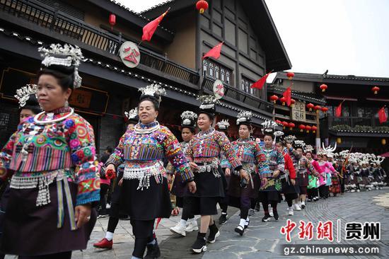 图为在乐透世界省丹寨县万达小镇景区,苗族妇女参加民俗服饰巡游表演。 黄晓海 摄