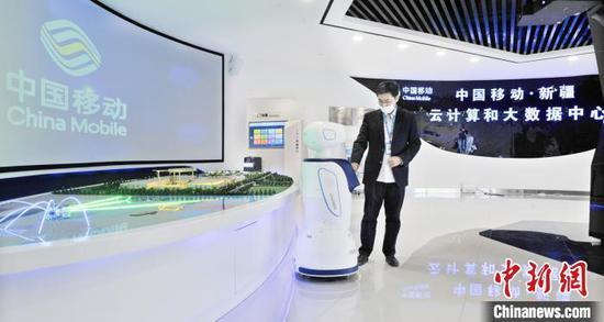 中国移动(新疆)云计算和大数据中心的员工正在操作机器人。约提克尔·尼加提