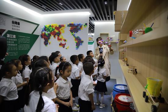 """瓯海区垃圾分类体验馆讲解员为孩子们上""""垃圾分类课""""。温州市综合行政执法局供图"""