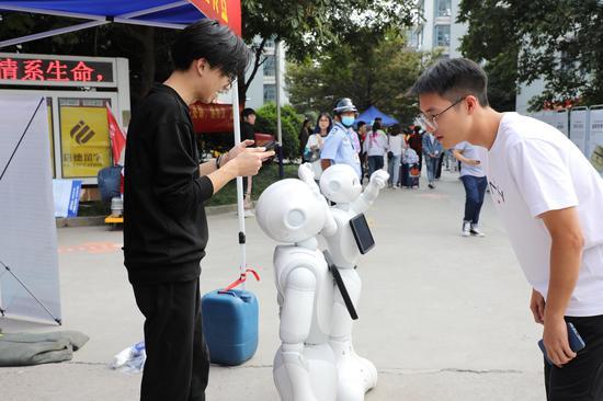 迎新机器人与学生沟通交流。 校方提供