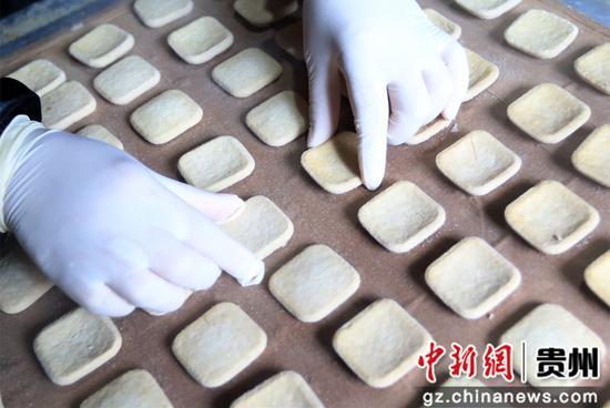 10月15日,在贵州省毕节市大方县对江镇龙场村豆香源食品厂,村民在摆放豆干。王纯亮  摄