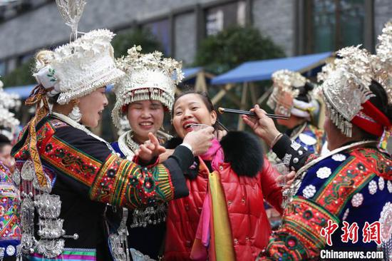 苗族同胞在吃新节长桌宴上给游客敬酒。 黄晓海 摄