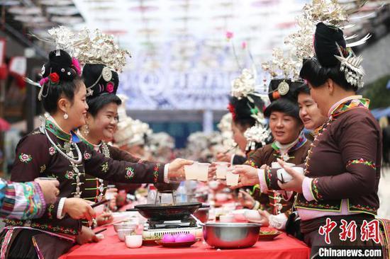 苗族同胞在吃新节长桌宴上相互敬酒。 黄晓海 摄