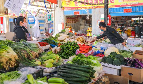 喀什市东湖社区菜市场内居民正在挑选蔬菜