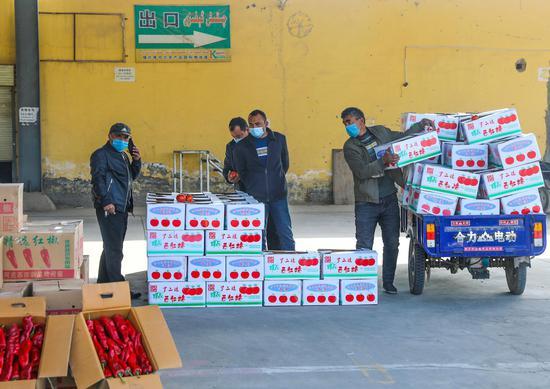 喀什市库克兰农产品批发市场内批发商正在卸货。