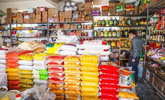 喀什市东湖社区内的一家粮油店内码放整齐的米面和食用油。