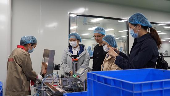 媒体记者在义乌一家美妆企业生产车间内采访、参观。  互腾(通讯员) 摄