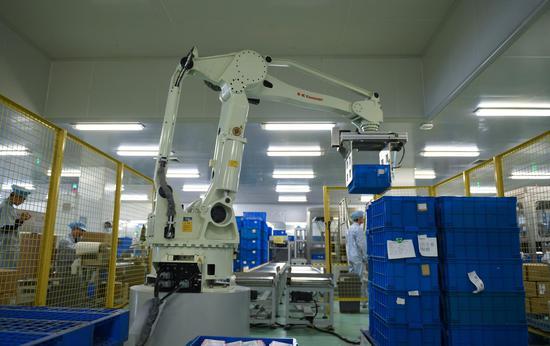 珀莱雅化妆品股份有限公司生产车间内自动化的机械臂在高效作业。王刚 摄