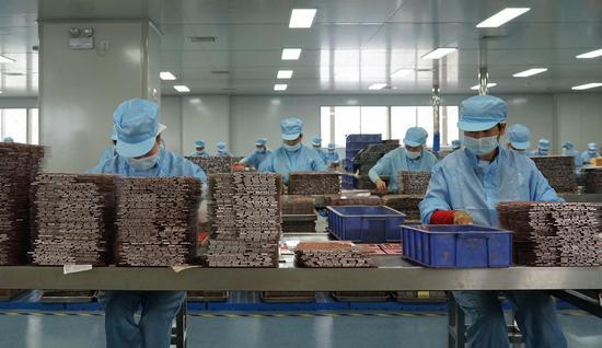 义乌一家美妆企业生产车间内,工作人员在流水线上作业。  互腾(通讯员) 摄